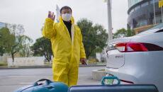 Kierowca w ochronnym ubiorze żegnający grupę Polaków, których dostarczył pod konsulat Francji w Wuhanie (PAP/Arek Rataj)